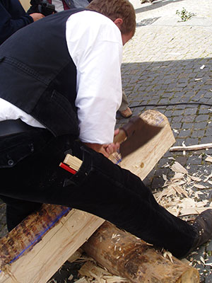 A German carpenter (Zimmerer) hewing a log into a beam. Note the blue ch: lk line snapped on the log to which the hewer works. Image © Patrick-Emil Zörner via Wikimedia Commons